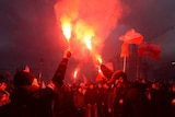 Demonstrators burn flares and wave Polish flags during a far-right march in Warsaw.