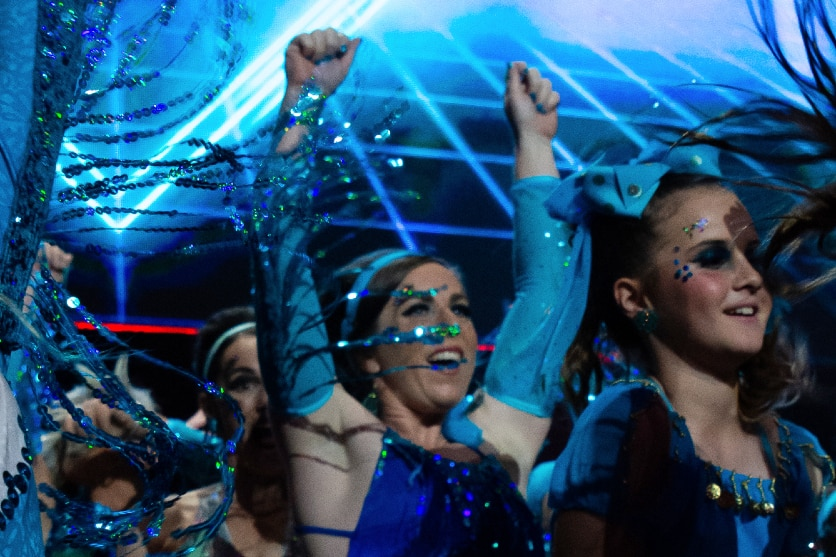 Adults on stage in blue costumes and stage lights with hands in air
