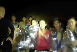 Spotlight shines on a group of boys wrapped in silver thermal blankets and a navy diver wearing black