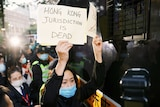 A woman wearing a mask holds a sign saying Hong Kong jurisdiction is dead with people gathered behind her.