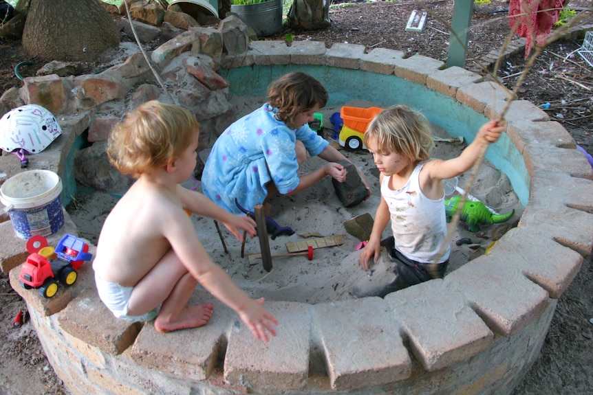 A toddler wearing only a nappy sitting on the edge of the sandpit watching his older sisters playing, holding a stick and a rock