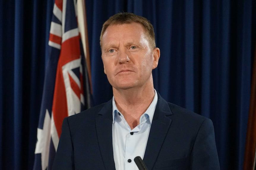 Paul Kirby stands near the Australian flag