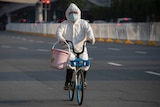 A resident wearing mask and suit against the coronavirus cycles in Wuhan.