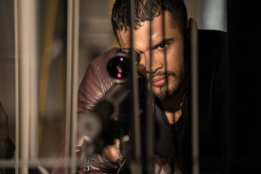 A man with serious and focused expression drips with sweat lies on ground hold weapon and looking through rifle scope.