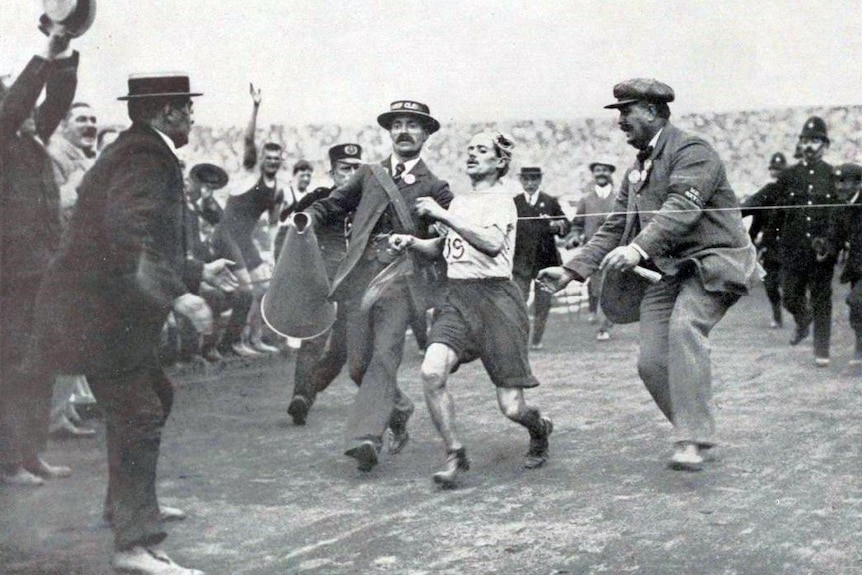 A man in shorts and a t-shirt crossing a finishing line while surrounded by men in suits and hats