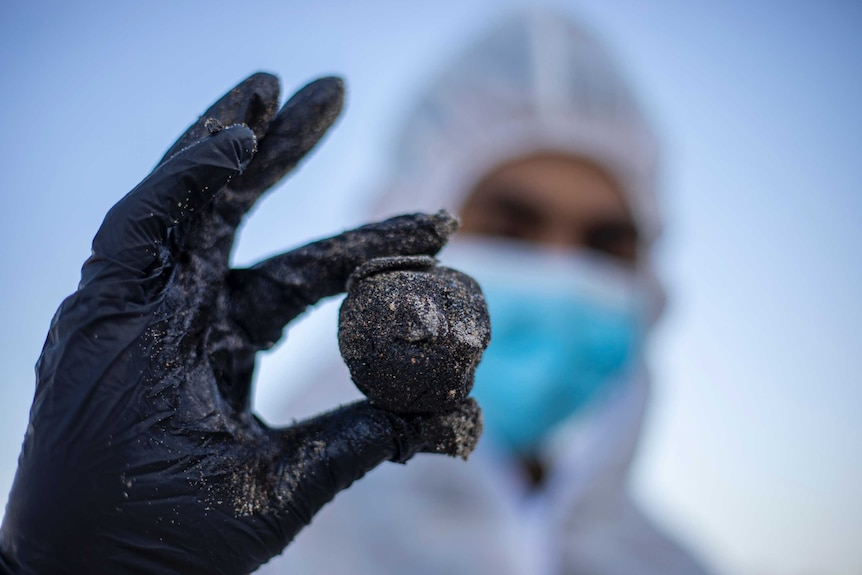 A man in protective gear holds up a glob of tar