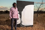 Artist Timo Hogan stands outside next to his award-winning painting.