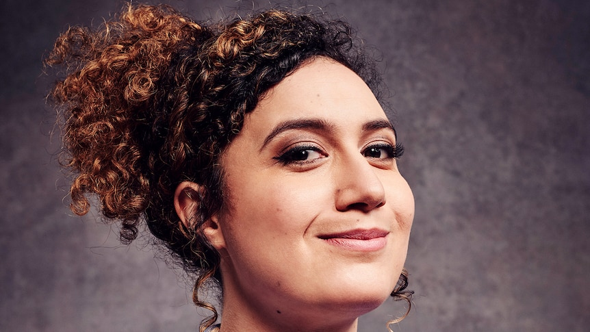 Rose Matafeo, her curly hair tied back, smiles proudly, with her arms folded