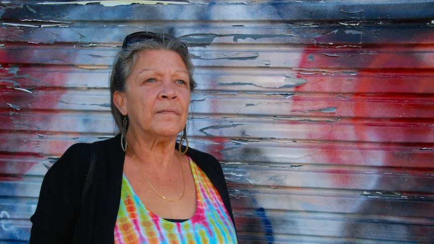Older Indigenous woman against colourful background.