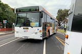 A bus replacing train services pulls out from a stop.