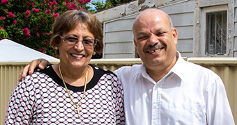 Reifat Botros and his wife Ezis Botros stand in their backyard.