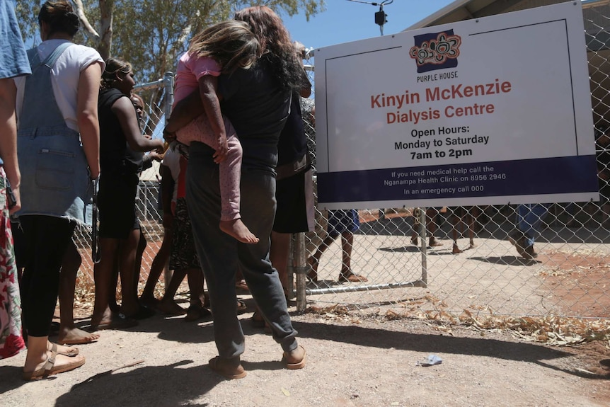 People queue outside a fence which features a sign that reads 'Kinyin McKenzie Dialysis Centre'.