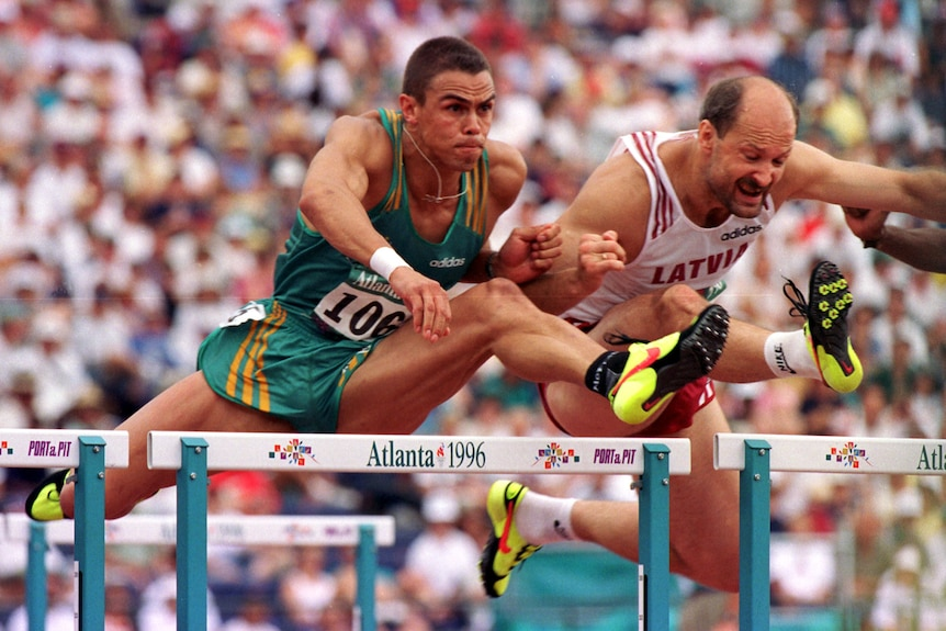 Two men competing in a hurdling event at track and field competition
