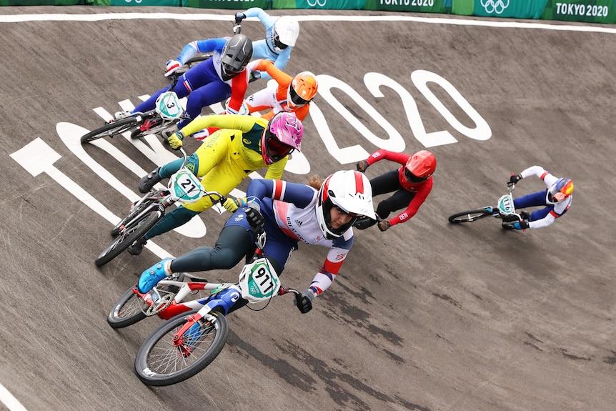 Seven women wearing bike helmets ride bikes on a road