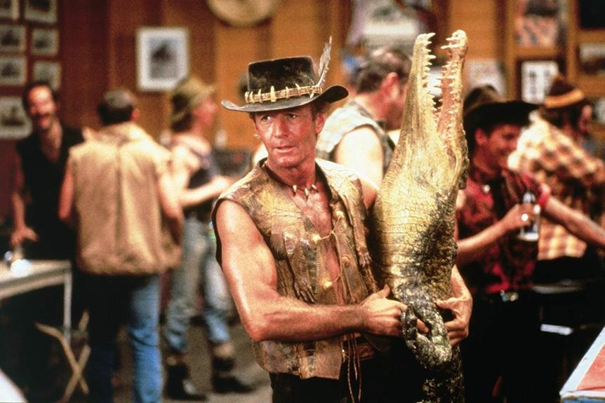 A still of Paul Hogan holding a crocodile from the 1986 film Crocodile Dundee