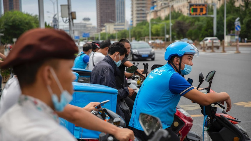 Delivery drivers wearing face masks to protect against the coronavirus wait to cross an intersection in Beijing.