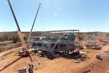 A wide shot of the Mt Marion lithium mine with a crane to the left of the mine structure.