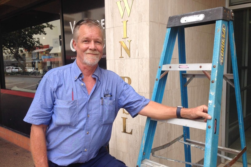 Security system installer Matthew Donogue with a ladder outside a Darwin business
