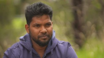 Thanush Selvarasa wearing a navy jacket with greenery in the background.