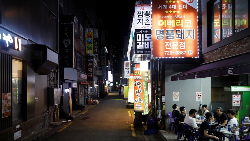 People drink outside on the side of a narrow street in Seoul, South Korea.
