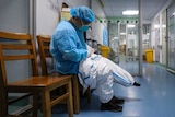 A doctor sits on a chair and puts on a quarantine suit