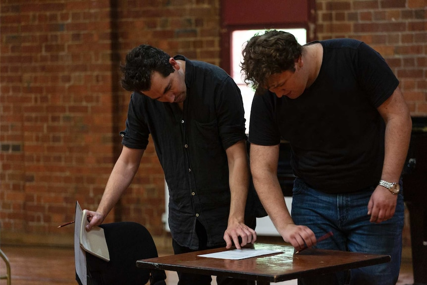 Two men looking at a script in a rehearsal for a play