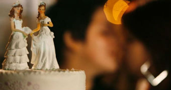 A wedding cake has two bride ornaments standing on top of it and a blurred same-sex couple kisses in the background.