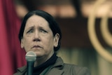 Ann Dowd holds a microphone with a pained look on her face.