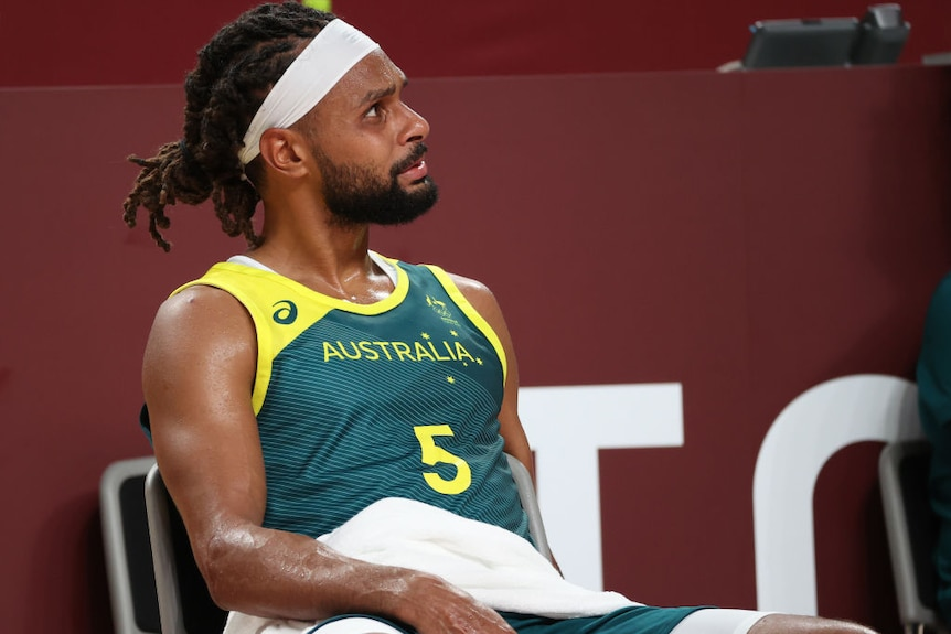 Australian basketballer patty mills sits on a chair with a towel looking like he is about to cry