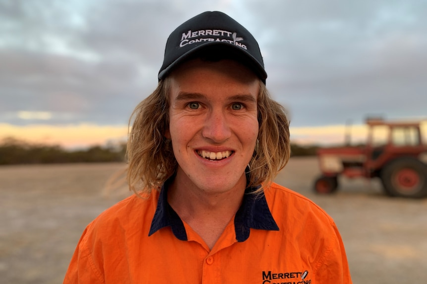 A white man with shoulder-length blonde hair looks to the camera and smiles. He wears an orange high-vis top and black cap.