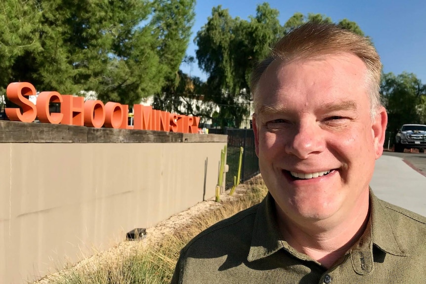 Pastor Shawn Thornton in front of the school ministry sign