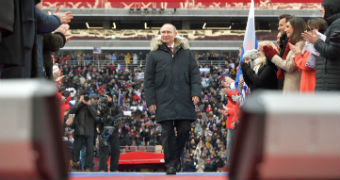 Vladimir Putin walks among supporters applauding him
