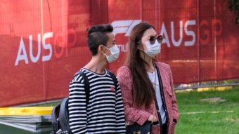 A man and woman wearing surgical masks stand outside at the Australian F1 Grand Prix.