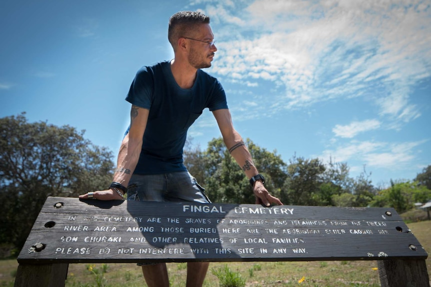 ABC RN Presenter for Awaye! Daniel Browning is leaning on a signpost of a cemetery in his hometown, Fingal