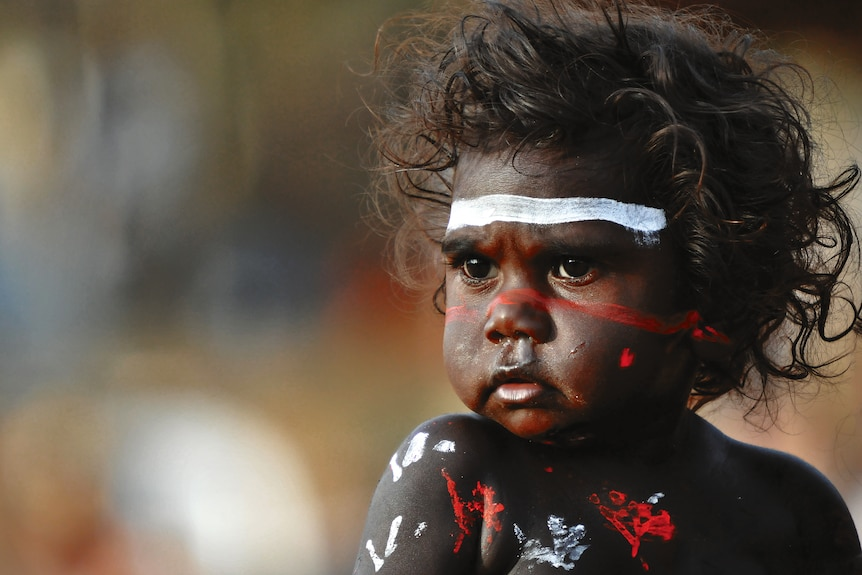 Close-up of Indigenous toddler, smiling, with coloured paint across their face.