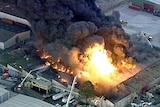 An aerial image shows flames and thick black smoke rising from a West Footscray warehouse.