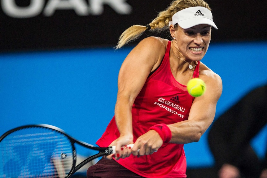 Kerber grips the racket and grits her teeth as she goes to hit the ball.
