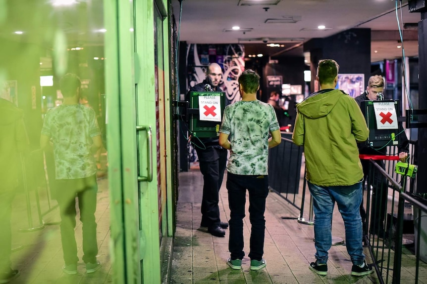 Two men having their ID's scanned by bouncers at a Brisbane nightclub.