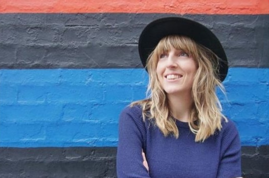 A woman with long blonde hair, black hat and navy jumper stands against coloured painted wall looking up and smiling widely.