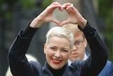 Maria Kolesnikova smiles as she makes a heart shape with her hands.