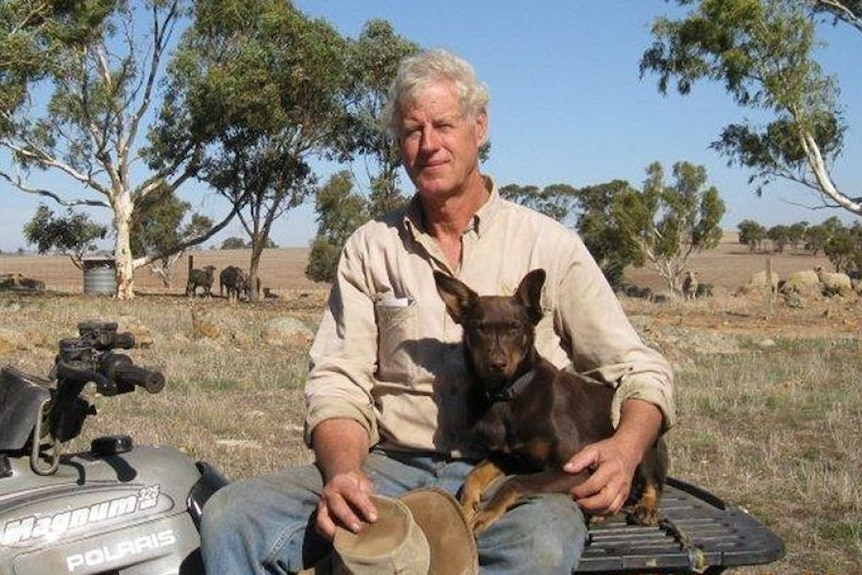White, middle-aged man with grey hair, wearing a shirt and sitting on a quad bike and a red kelpie dog