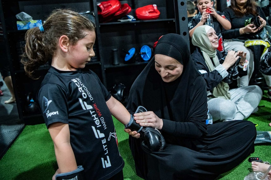 A mother helps her son put on his boxing gloves.
