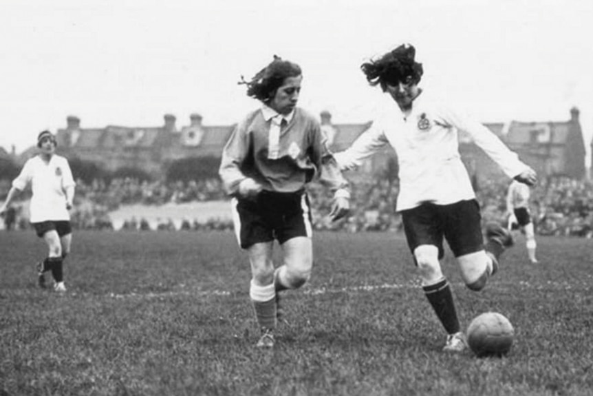 Two women playing soccer in the 1920s.
