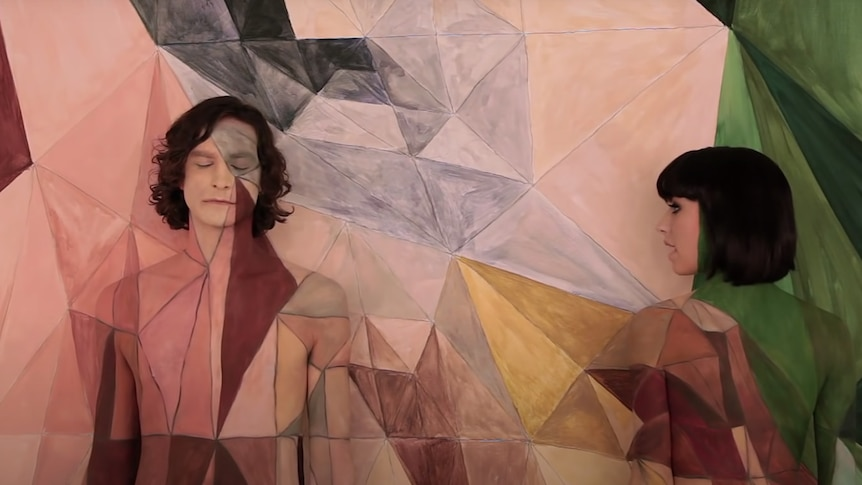 Gotye and Kimbra are topless and painted the same colours and pattern as the wall behind them