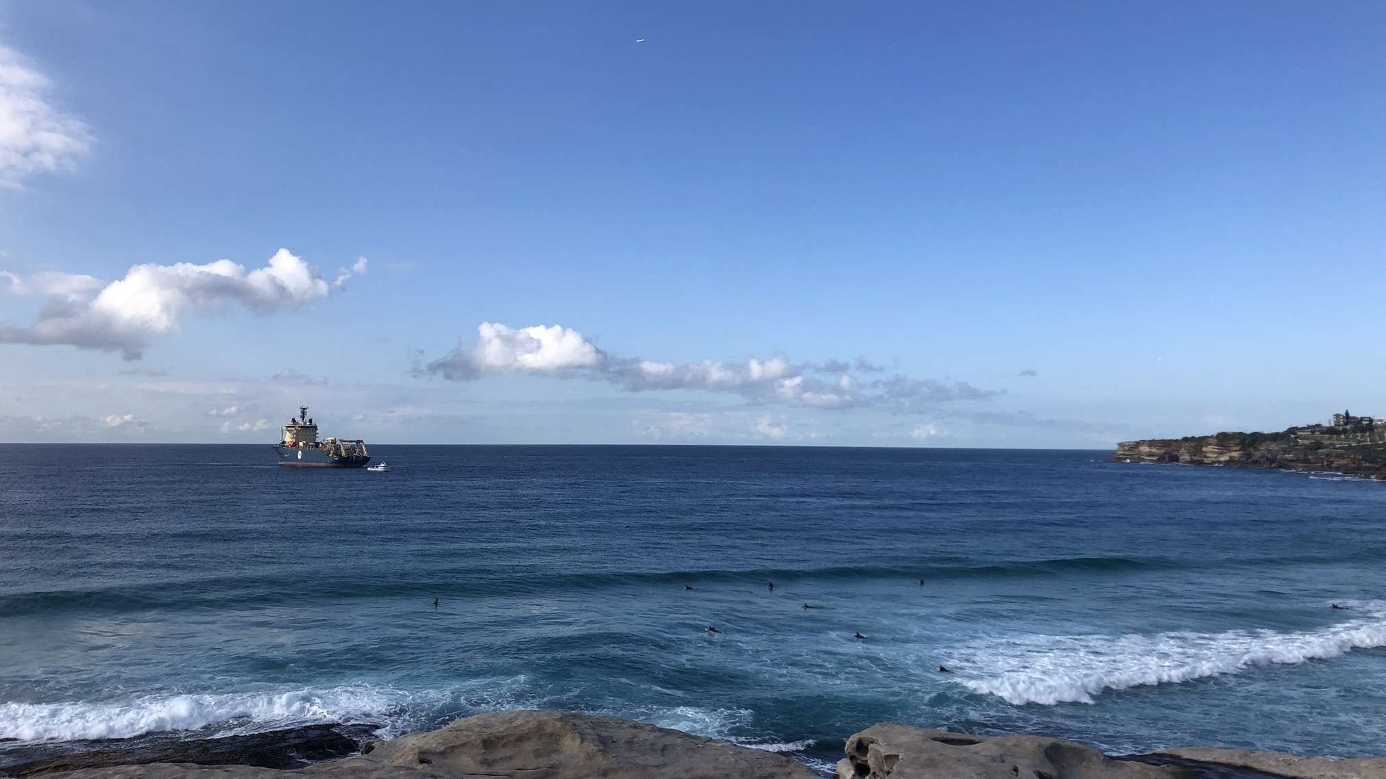A large cable laying ship is seen quite close to the cliffs at Tamarama.