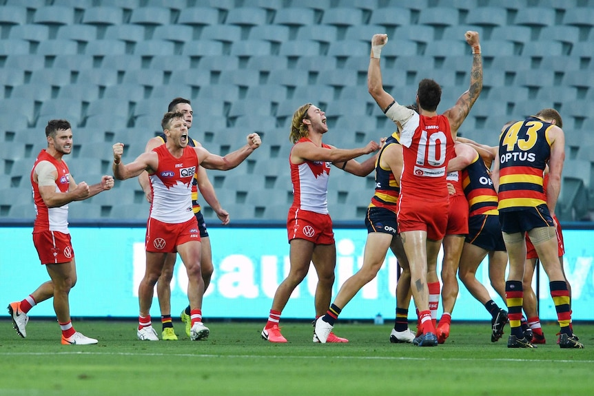 Sydney Swans players celebrate after the full-time siren against Adelaide Crows in the AFL.
