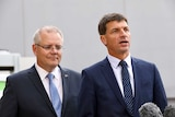 Angus Taylor speaks to media as PM Scott Morrison looks on from behind