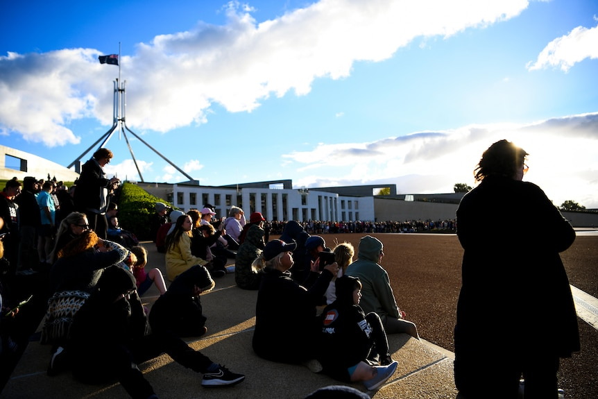 people sit together on a step in the day outside parliament house when the flag in the distance
