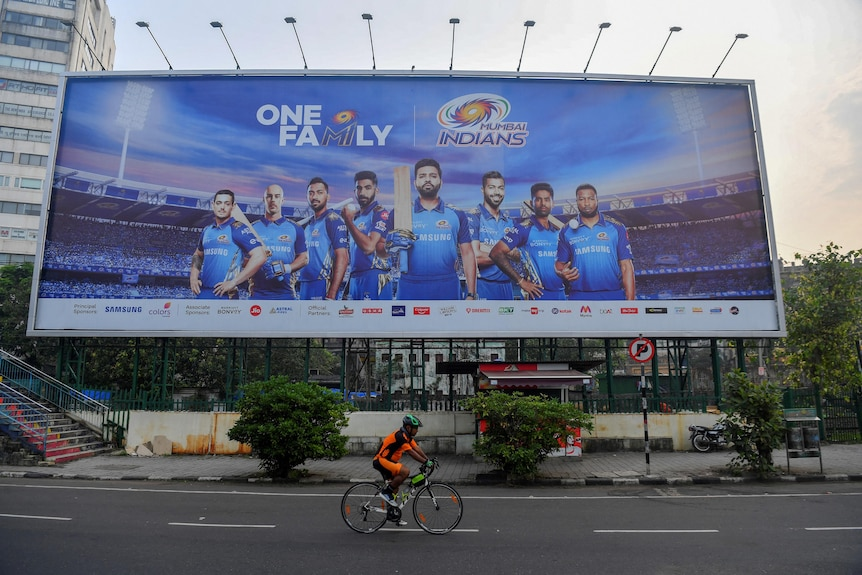 A cyclist rides in front of a large billboard, which has a number of Mumbai Indians players on it
