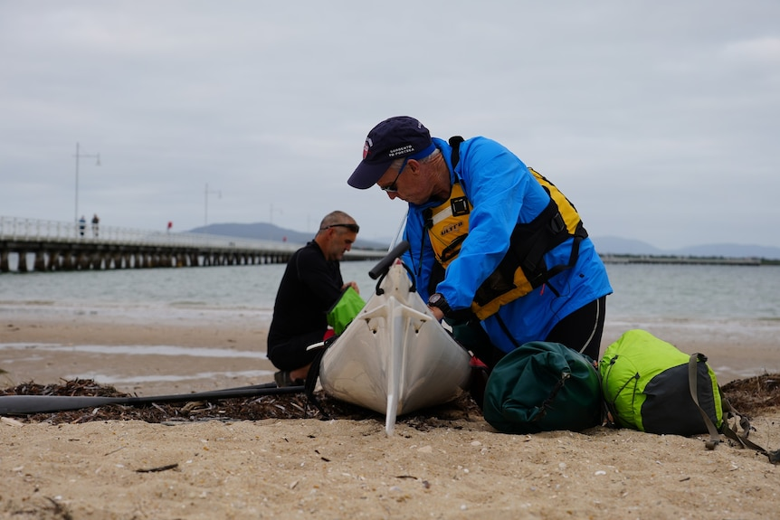 Two men packing goods into a kayak on the shore.